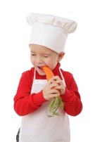 Little chief-cook tasting the carrot isolated on white