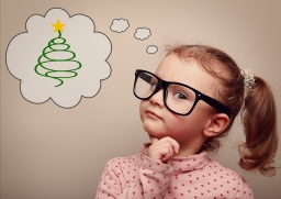 Cute kid girl in glasses thinking about gift on Christmas holiday. Vintage portrait